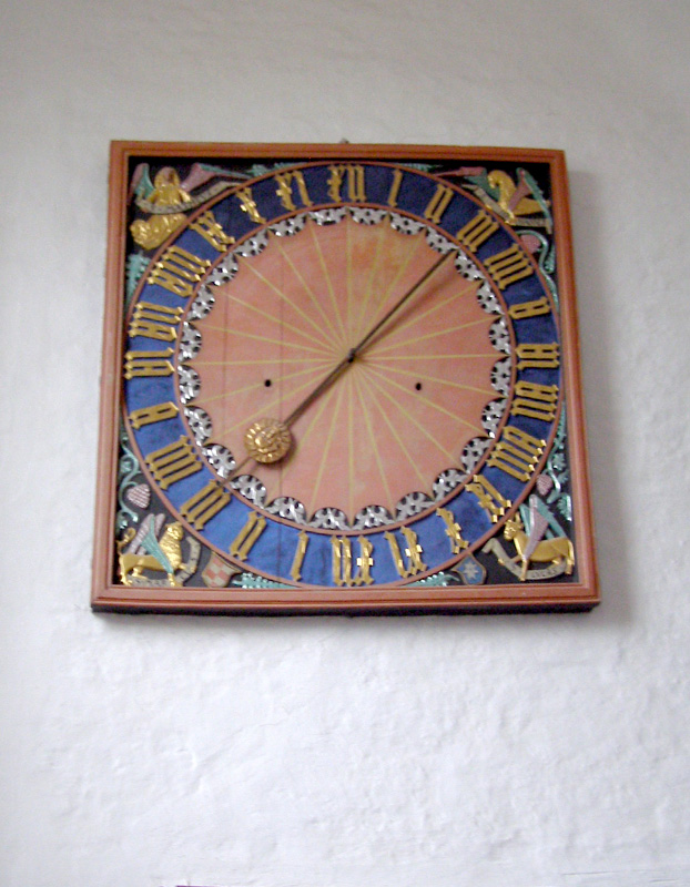 A 24-hour clock hangs by the entrance in the Aarhus Cathedral.